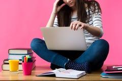 Ragazza che studia per i suoi esami a casa, studente che si siede sul suo scrittorio con il computer portatile nel suo rivestimen Fotografia Stock