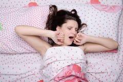 Ragazza che sveglia gli sbadigli e gli allungamenti Fotografie Stock