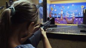 Ragazza che tende con il fucile di aria nella galleria di fucilazione archivi video