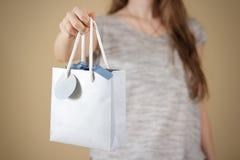 Ragazza che tiene derisione in bianco disponibila della borsa del regalo della carta blu su PA vuoto Fotografie Stock