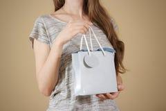 Ragazza che tiene derisione in bianco disponibila della borsa del regalo della carta blu su PA vuoto Immagini Stock Libere da Diritti