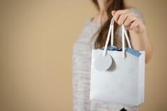 Ragazza che tiene derisione in bianco disponibila della borsa del regalo della carta blu su PA vuoto Immagini Stock