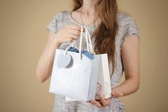 Ragazza che tiene derisione di carta della borsa del regalo dello spazio in bianco due disponibili su Pac vuoto Fotografia Stock