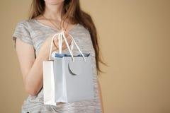 Ragazza che tiene derisione di carta della borsa del regalo dello spazio in bianco due disponibili su Pac vuoto Fotografie Stock