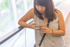 Ragazza che tiene gli occhi sullo smartphone alla scala mobile immagini stock