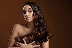 Ragazza che tiene i suoi capelli ricci Fotografie Stock