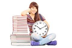 Ragazza che tiene il grande orologio di parete accanto alla pila di libri Fotografia Stock Libera da Diritti