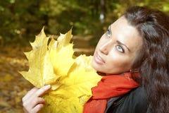 Ragazza che tiene le foglie di giallo Fotografia Stock