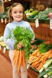 Ragazza che tiene mazzo di carote nel negozio dell'azienda agricola Fotografia Stock Libera da Diritti