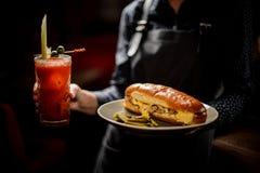 Ragazza che tiene piatto bianco con il panino saporito della carne ed il cocktail red delicious immagini stock