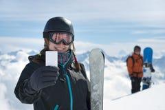 Ragazza che tiene sorridere in bianco del biglietto dello sci Fotografia Stock