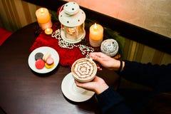 Ragazza che tiene tazza dei maccheroni del dessert e del cappuccino sul piatto Fotografie Stock Libere da Diritti