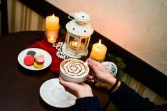 Ragazza che tiene tazza dei maccheroni del dessert e del cappuccino sul piatto Fotografie Stock
