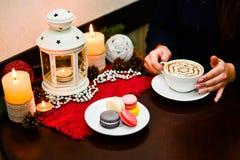 Ragazza che tiene tazza dei maccheroni del dessert e del cappuccino sul piatto Immagine Stock