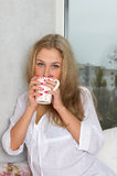 Ragazza che tiene tazza e che guarda attraverso la finestra Fotografia Stock