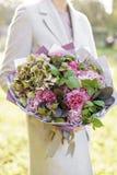 Ragazza che tiene un bello mazzo della molla disposizione dei fiori con le rose del giardino e dell'ortensia Viola di colore lumi fotografia stock