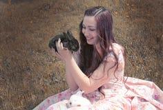 Ragazza che tiene un coniglio nero Fotografia Stock Libera da Diritti