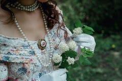 Ragazza che tiene un fiore in sua mano fotografia stock