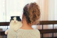 Ragazza che tiene un gatto sulla sua spalla a casa fotografie stock