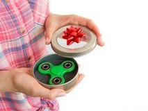 Ragazza che tiene un giocattolo colourful del filatore di irrequietezza della mano in un contenitore di regalo Immagine Stock Libera da Diritti