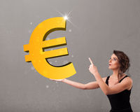 Ragazza che tiene un grande segno dell'euro dell'oro 3d Fotografia Stock Libera da Diritti