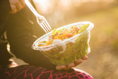 Ragazza che tiene un'insalata sul tramonto fotografie stock