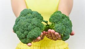 Ragazza che tiene un'insalata verde dei broccoli in sue mani estendendo le vostre armi in avanti con fotografia stock