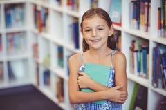 Ragazza che tiene un libro in biblioteca Fotografia Stock