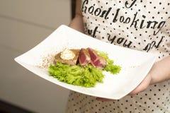 Ragazza che tiene un piatto di alimento Fotografia Stock