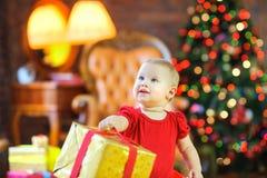 Ragazza che tiene un regalo da un nastro rosso, contro lo sfondo di un albero di Natale festivo immagini stock