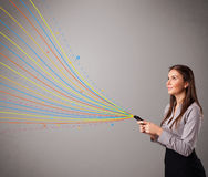 Ragazza che tiene un telefono con le linee astratte variopinte Fotografia Stock Libera da Diritti