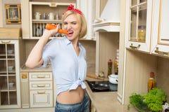 Ragazza che tiene una grande carota nella cucina Fotografia Stock