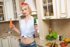 Ragazza che tiene una grandi carota e cetriolo in Fotografie Stock Libere da Diritti