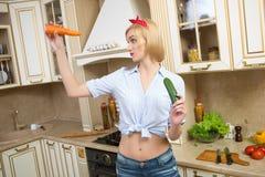 Ragazza che tiene una grandi carota e cetriolo in Fotografia Stock Libera da Diritti