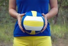 Ragazza che tiene una palla variopinta di sport per pallavolo Foto del primo piano Immagini Stock Libere da Diritti
