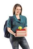 Ragazza che tiene una pila di libri e una mela sulla cima Immagini Stock Libere da Diritti