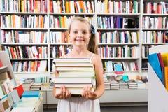 Ragazza che tiene una pila di libri in una libreria Fotografie Stock