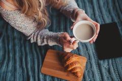 Ragazza che tiene una tazza del cacao sul letto immagini stock libere da diritti