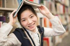 Ragazza che tiene uno scaffale per libri vicino sopraelevato del libro Fotografia Stock Libera da Diritti