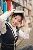 Ragazza che tiene uno scaffale per libri vicino sopraelevato del libro Fotografie Stock