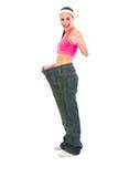 Ragazza che tira i jeans di grande misura e che mostra i pollici in su Fotografie Stock