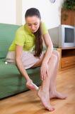 Ragazza che tratta i piedi con l'unguento Immagine Stock