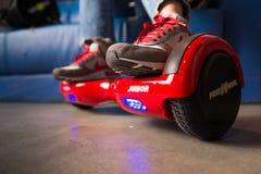 Ragazza che usando un bordo a due ruote di equilibrio rosso Il giroscopio ha basato la ruota doppia s elettrica Fotografia Stock Libera da Diritti