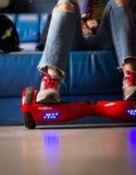 Ragazza che usando un bordo a due ruote di equilibrio rosso Il giroscopio ha basato la ruota doppia s elettrica Immagine Stock