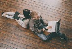 Ragazza che usando una compressa e un ragazzo con un computer portatile Fotografie Stock