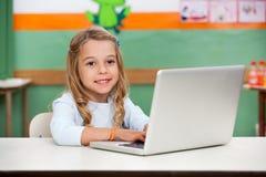 Ragazza che utilizza computer portatile nell'aula Fotografie Stock