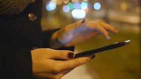 Ragazza che utilizza il pc della compressa all'aperto nella città alla notte Bello traffico cittadino di notte della sfuocatura a archivi video