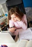 Ragazza che utilizza telefono cellulare invece di studio nella camera da letto Fotografie Stock