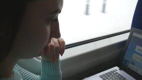 Ragazza che viaggia in un treno e che per mezzo del taccuino Schermo premuroso del computer portatile di sguardo della donna Movi video d archivio