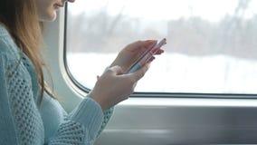 Ragazza che viaggia in un treno e che per mezzo del telefono cellulare La bella donna invia un messaggio dallo smartphone attraen Fotografia Stock